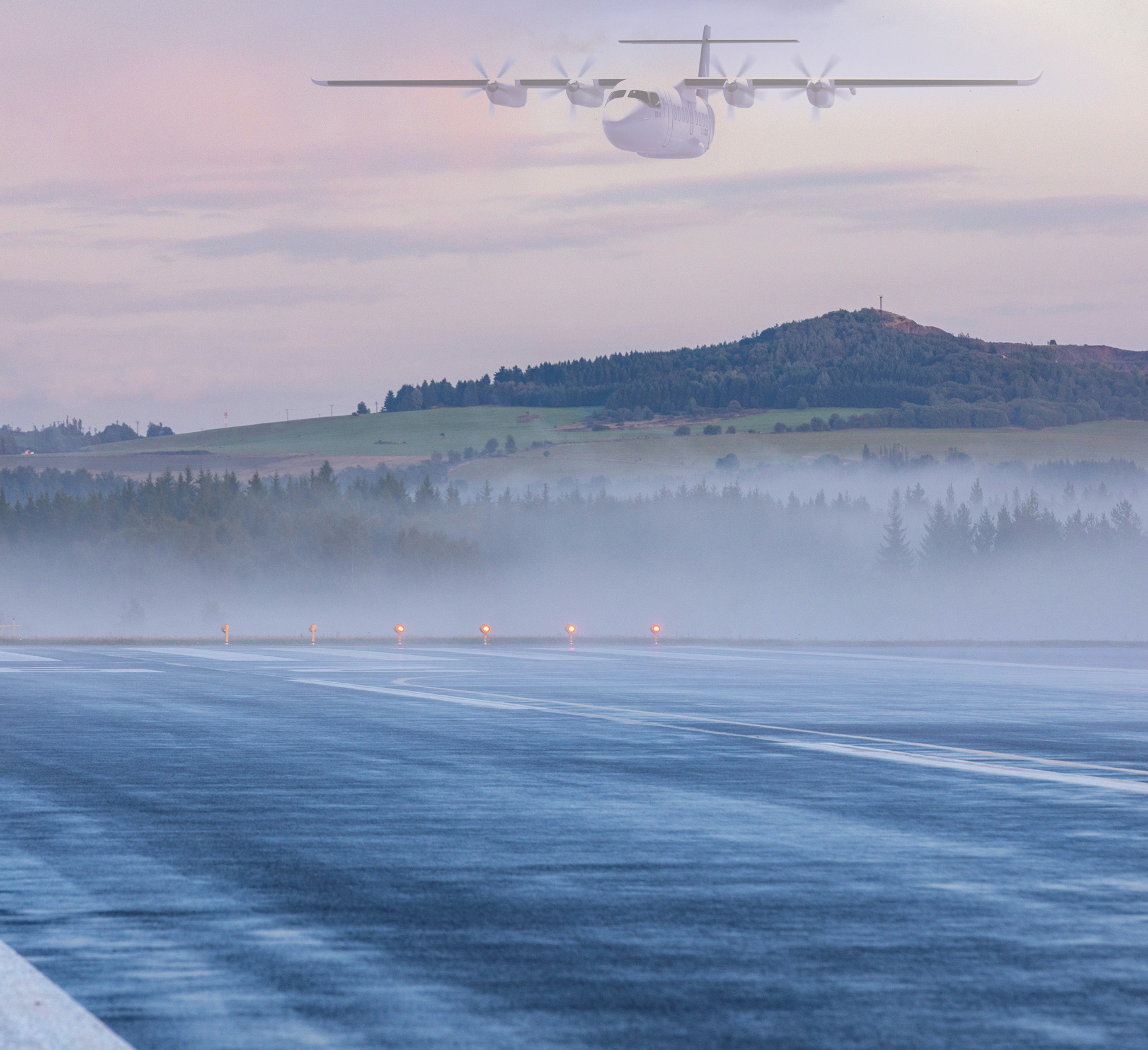Empty runway at airport during a foggy sunrise